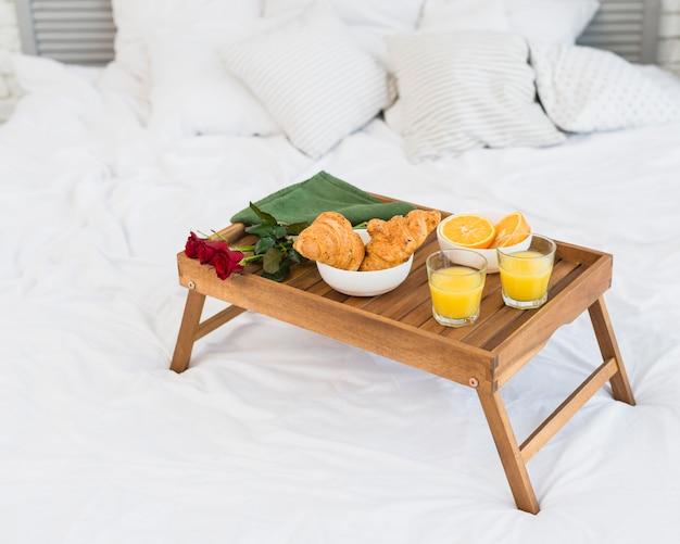 Voedsel en rozen op ontbijttafel op bed