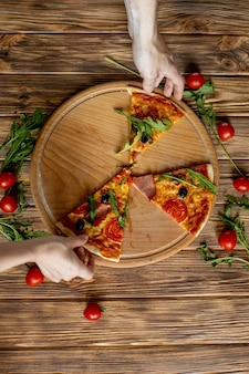 Voedsel eten. close-up van mensen handen nemen plakjes pepperoni pizza.