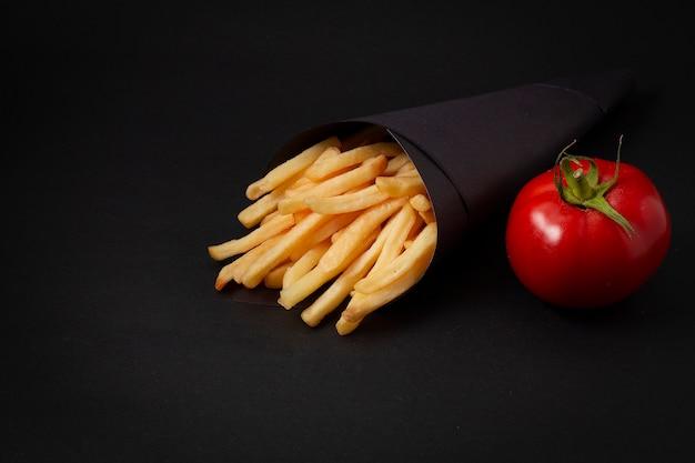 Voedsel frietjes op een zwarte tafel, met tomaat, in een zwart pakket
