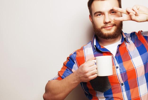Voedsel, geluk en mensen concept: jonge, bebaarde man met een kopje koffie tegen een grijze achtergrond