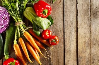 Voedsel groente kleurrijke achtergrond. Lekkere verse groenten op houten tafel. Bovenaanzicht met kopie ruimte.