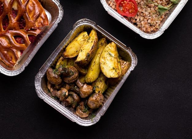 Voedsel in containers. gebakken aardappel met champignons. van bovenaf bekijken .. levering concept.