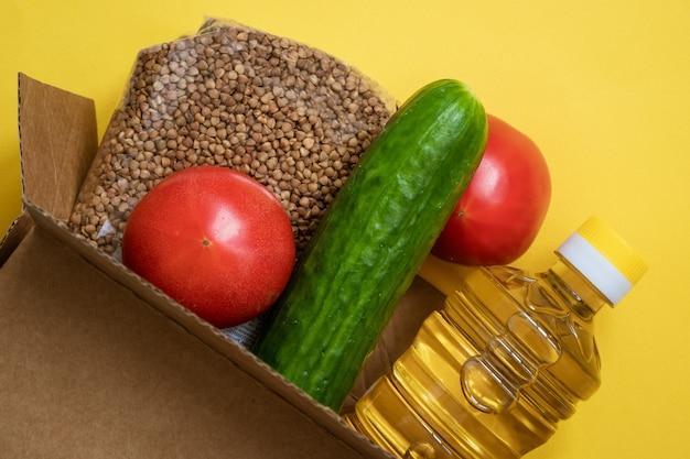 Voedsel in een kartonnen doos op een gele achtergrond