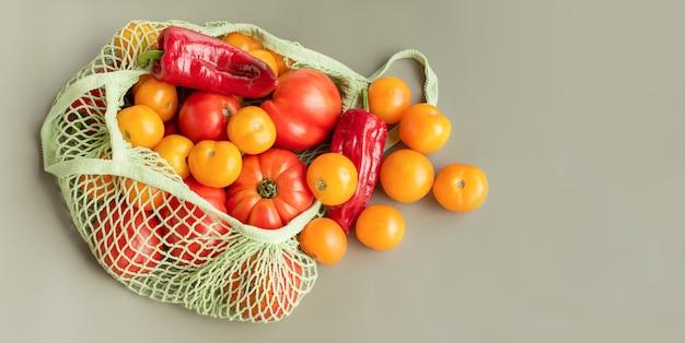 Voedsel in groene ecologische zak. groenten gele en rode tomaten en paprika's in een raster.