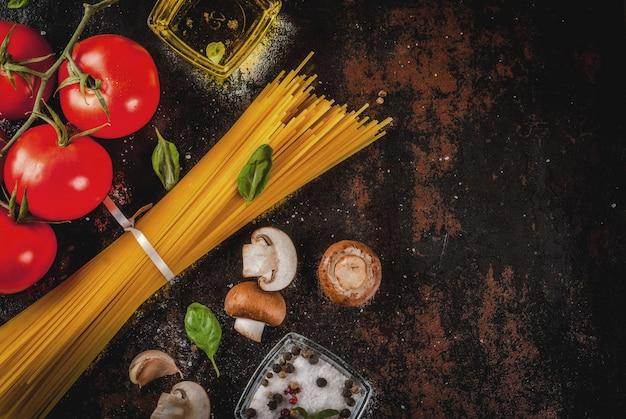 Voedsel, ingrediënten voor het koken van het diner. pasta spaghetti, groenten, sauzen en kruiden, donker roestig bovenaanzicht