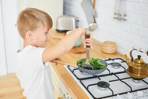 Voedsel, kinderen en koken concept. portret van knappe schooljongen in wit t-shirt permanent aan het aanrecht met behulp van fornuis om te koken, metalen draaier te houden, groene bladeren op koekenpan stoven