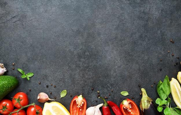 Voedsel koken achtergrond op zwarte tafel. verse groenten, specerijen, kruiden. ingrediënten om te koken
