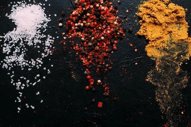Voedsel kruiden zout mosterd peper kurkuma donkere achtergrond concept