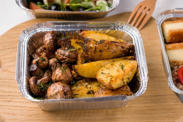 Voedsel levering concept. container met champignons en aardappelen op een houten bord