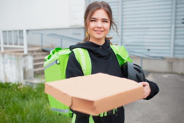 Voedsel levering concept. de pizza delivery woman heeft een groene koelkastrugzak.