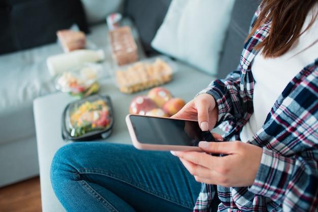 Voedsel levering concept. een jonge vrouw geeft opdracht tot voedsel thuis gebruikend een smartphone.