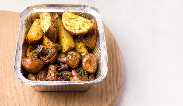 Voedsel levering concept. gebakken aardappelen met champignons in een bakje.