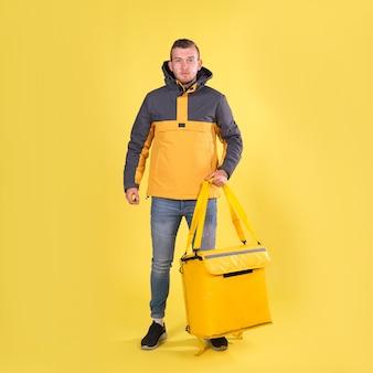 Voedsel levering lachende blanke jonge man in geel jasje en met thermoszak op zijn schouders op geel