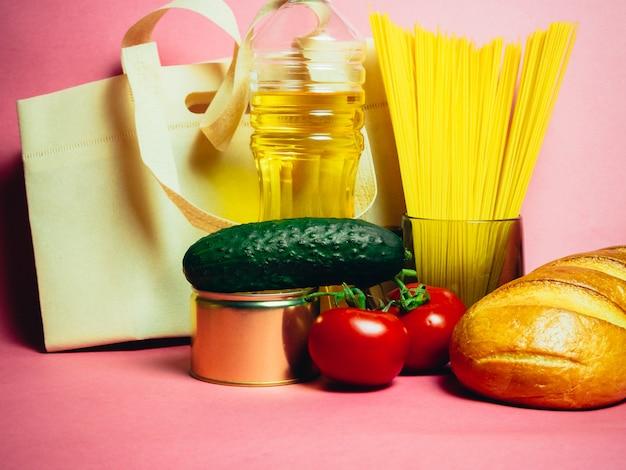 Voedsel levert crisis voedselvoorraad voor quarantaine-isolatieperiode op roze. vermicelli, pasta, conserven, bananen, boter, brood.