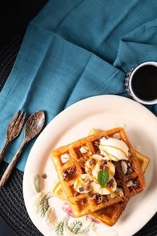 Voedsel maaltijd ontbijt concept zelfgemaakte biologische wafels banaan vanille-ijs topping met karamelsaus op zwarte achtergrond met kopie ruimte