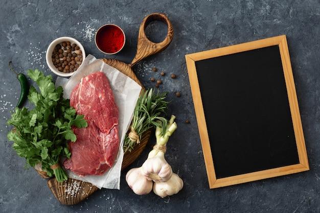 Voedsel menu. kooktafel met leeg schoolbord en rundvlees, groenten, kruiden, kruiden bovenaanzicht