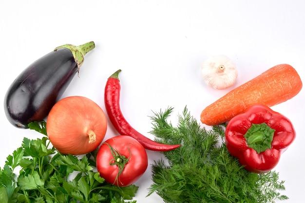 Voedsel muur. seizoensgebonden groenten en greens op een witte tafel. bovenaanzicht, plat gelegd
