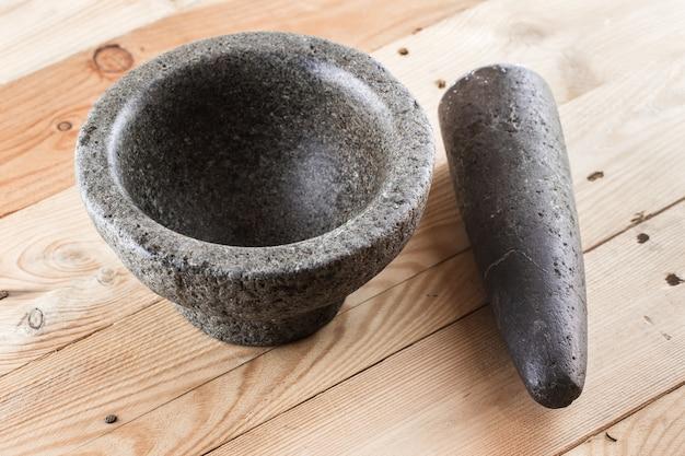 Voedsel stenen mortier en een stamper op houten achtergrond