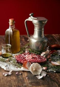 Voedsel: uien, romero, vleesbiefstuk, zout, peper, knoflook, olijfolie, vork, worstjes