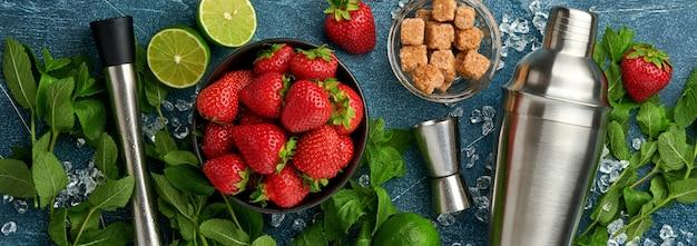 Voedsel verse ingrediënten voor het maken van limonade, doordrenkt detoxwater of cocktail. aardbeien, limoen, munt, basilicum, rietsuiker, ijsblokjes en shaker op donkere steen of betonnen ondergrond. kopieerruimte bovenaanzicht
