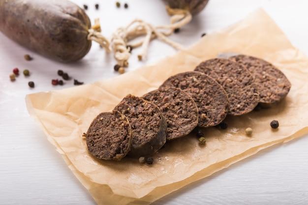 Voedsel, vlees en heerlijk concept - worsten gemaakt met paardenvlees met soorten en groenten.