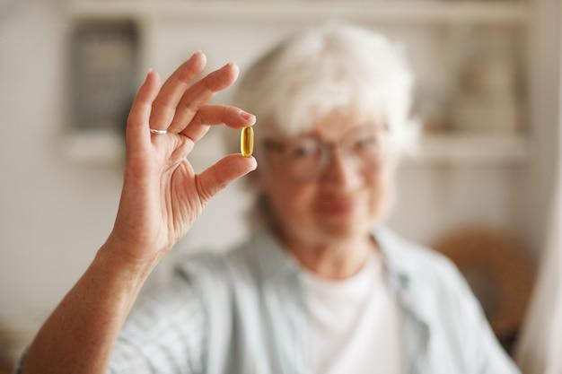 Voedsel, voeding, dieet en gezondheidsconcept. close-up shot van de hand van een oudere vrouw met visolie of omega-3 meervoudig onverzadigd vetzuursupplement in de vorm van een capsule, die tijdens de lunch wordt ingenomen