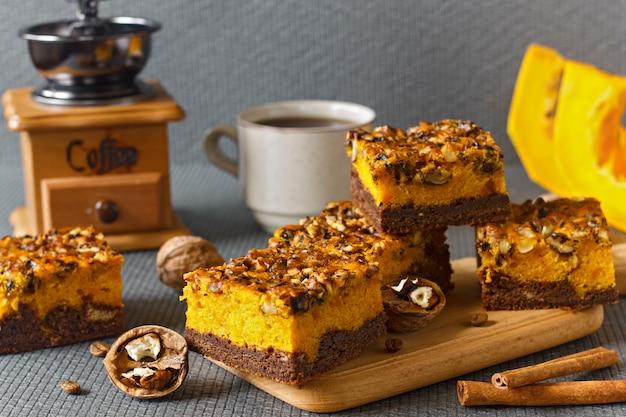Voedsel voor halloween. zelfgemaakte chocolade brownie met noten en een laag pompoen. koffie met gebak.