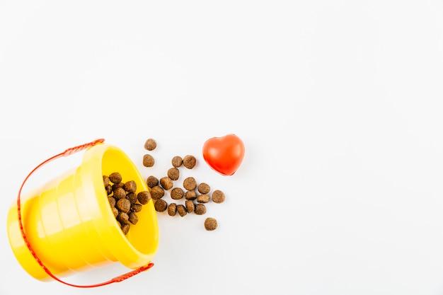 Voedsel voor huisdieren in emmer op witte oppervlakte