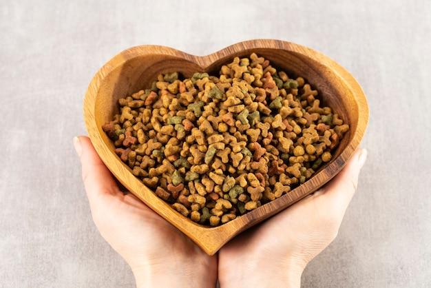 Voedsel voor huisdieren in hartvormige kom in handen van de vrouw