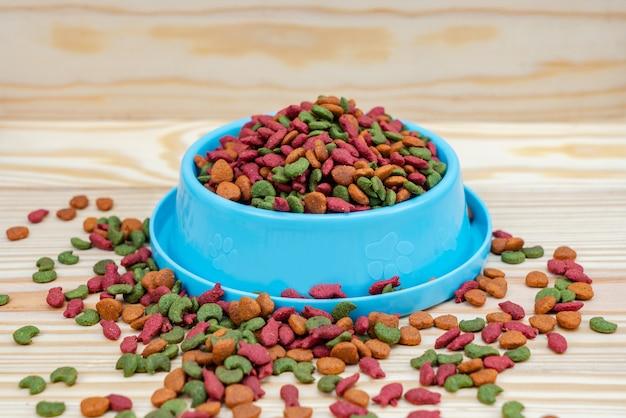 Voedsel voor huisdieren in kom op houten achtergrond