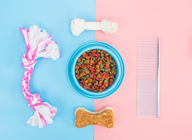 Voedsel voor huisdieren in kommen met bot, speelgoed, voor huisdieren op gekleurde achtergrond.