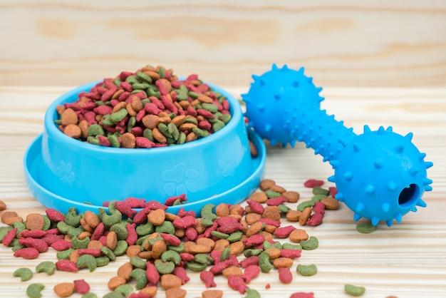 Voedsel voor huisdieren met rubberen speelgoed op houten achtergrond Premium Foto