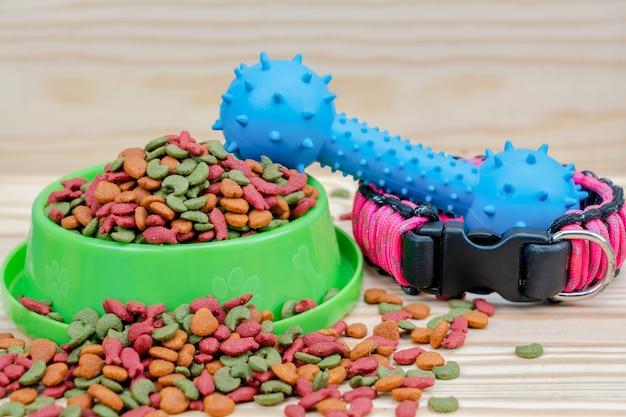 Voedsel voor huisdieren met rubberen speelgoed op houten achtergrond