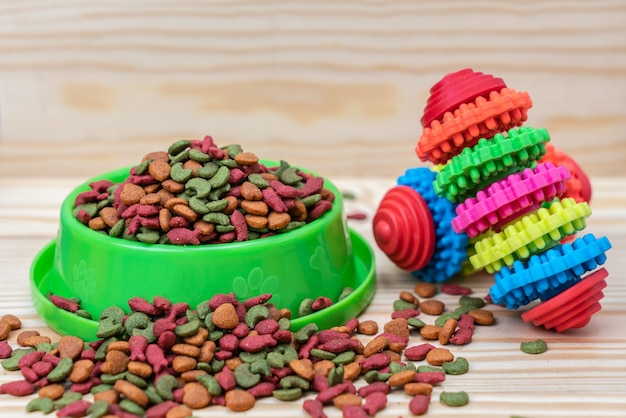 Voedsel voor huisdieren met rubberen speelgoed op houten tafel