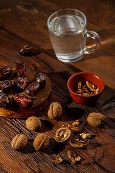 Voedsel voor iftar in ramadan vastende dadels, noten en water, op tafel. verticale foto