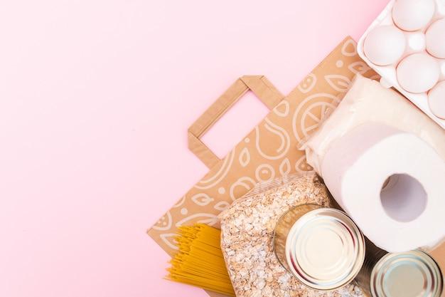 Voedsel voor quarantaine-isolatieperiode plat lag op gele ruimte met kopie ruimte. eieren, pasta, bonen, wc-papier, appel en wat seleals. crisis voedselvoorziening.