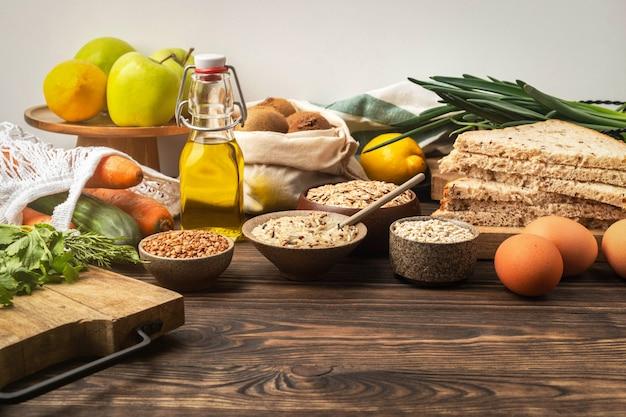Voedselachtergrond, groenten, fruit en graangewassen op een houten lijst in de keuken, gezonde kokende ingrediënten.