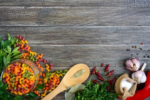 Voedselachtergrond - groenten, ruwe gekleurde deegwaren, kruiden. pasta met groenten.