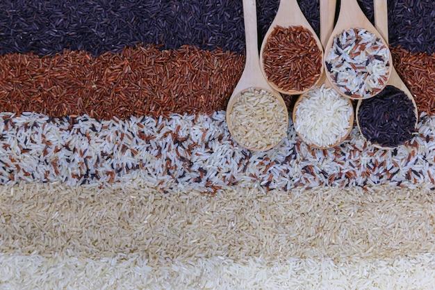 Voedselachtergrond met hoogste mening van vijf rijen van rijst in een houten lepel.
