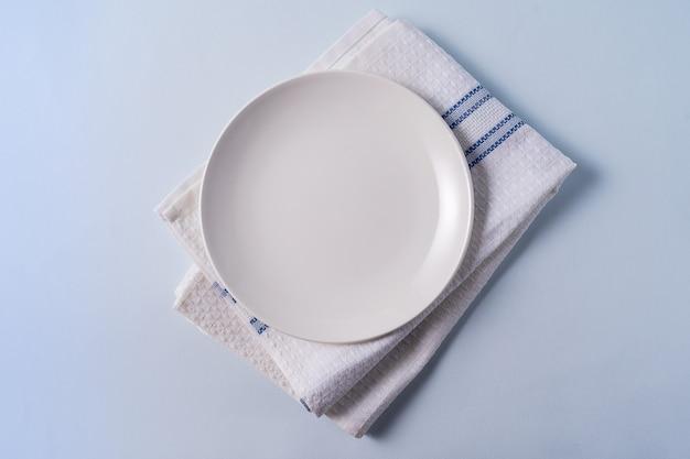 Voedselachtergrond met lege witte plaat over lichtblauw