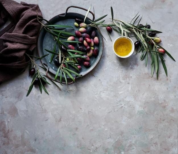 Voedselachtergrond met olijfboomtak, servet en plaat, mes en vorkbestek, olijfolie op concrete achtergrond