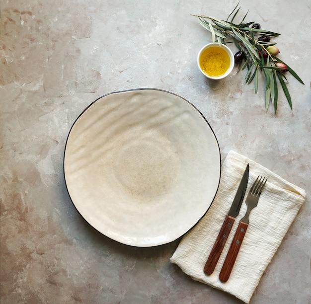 Voedselachtergrond met olijfboomtak, servet en plaat, messen en vorkbestek, olijfolie
