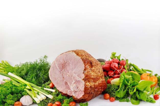 Voedselachtergrond met varkensvlees ham en gezonde verse groenten.