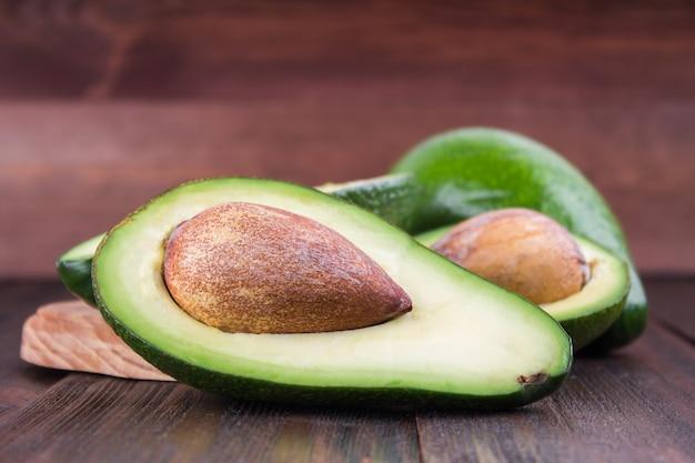 Voedselachtergrond met verse organische avocado op oude houten lijst,