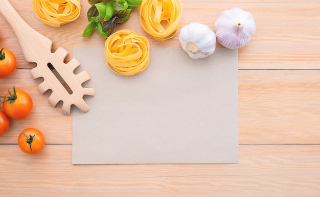 Voedselachtergrond voor smakelijke italiaanse gerechten met blanco pakpapier op houten achtergrond.
