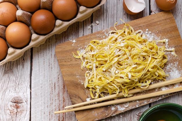 Voedselbereiding - rauwe eiernoedels met poedermeel op houten snijplank afgerond met eieren