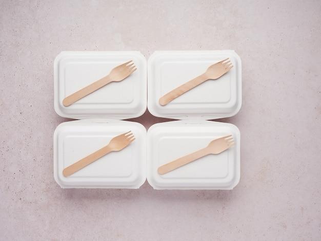 Voedselbezorgcontainers met houten lepel erop