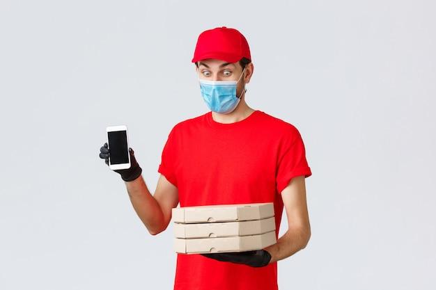 Voedselbezorging, applicatie, online boodschappen, contactloos winkelen en covid-19-concept. geamuseerde grappige koerier in rood uniform, gezichtsmasker en handschoenen, met smartphone-scherm-app en pizzadozen vast te houden