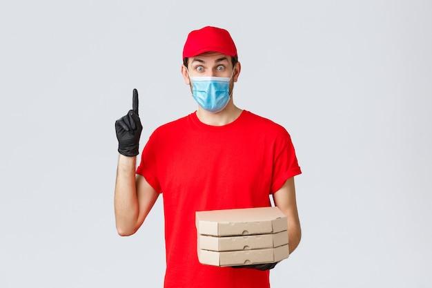 Voedselbezorging, applicatie, online boodschappen, contactloos winkelen en covid-19-concept. opgewonden bezorger in rood uniform, handschoenen en gezichtsmasker, heb suggestie, houd pizza vast en steek vinger op