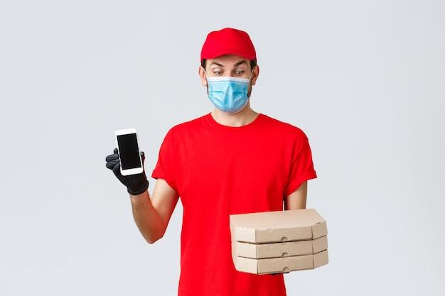 Voedselbezorging, applicatie, online boodschappen, contactloos winkelen en covid-19-concept. opgewonden koerier in rood uniform, geamuseerd naar pizzadozen kijkend, smartphonescherm-app of bonuspromo tonend